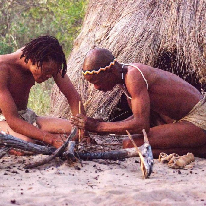 Bushmen at Deception Valley Lodge teach guests how to spark a fire by rubbing sticks together
